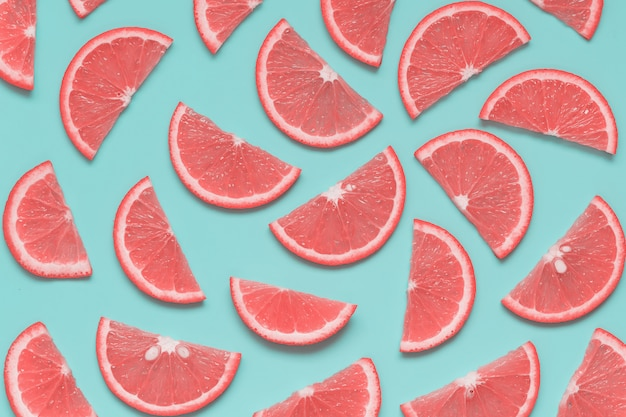 Modèle d'été créatif avec des tranches de pamplemousse sur fond bleu pastel