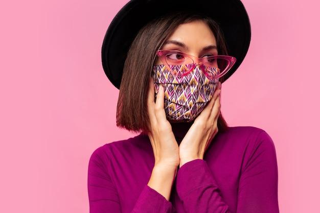 Modèle européen habillé de masque protecteur élégant. porter un chapeau noir et des lunettes de soleil.