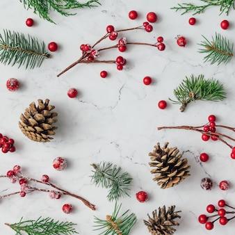 Modèle fait de branches d'arbres de noël, pommes de pin et baies rouges sur mur de marbre. concept de noël. mise à plat.