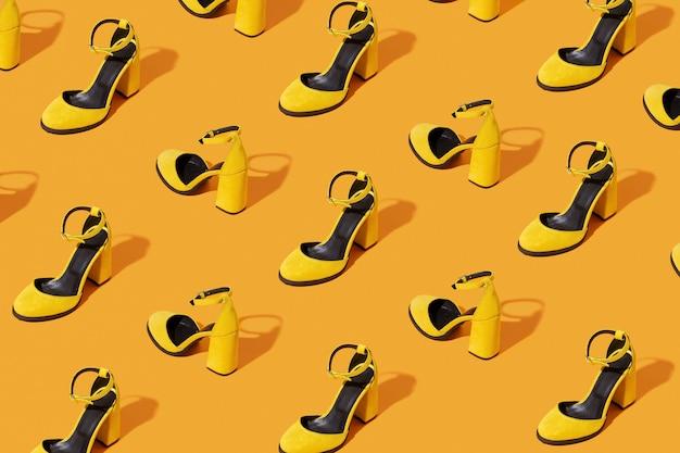 Modèle fait avec des chaussures en daim jaune sur fond orange. concept de mode minimal.