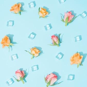Modèle fait de fleurs colorées et de glaçons sur bleu pastel. composition plat laïque de nature d'été minimale.
