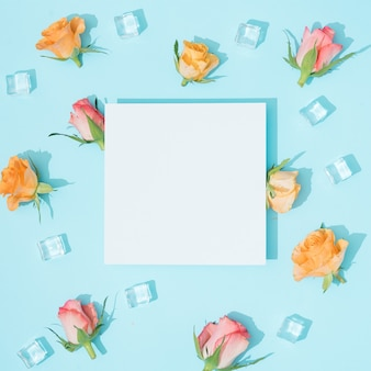 Modèle fait de fleurs colorées et de glaçons sur bleu pastel avec note de carte papier. composition plat laïque de nature d'été minimale.