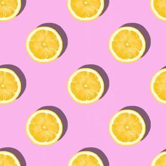 Modèle fait de tranches de citron sur fond rose, agrumes tropicaux