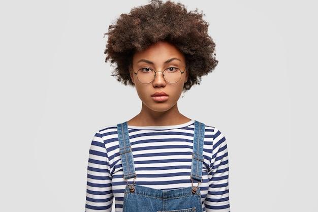 Modèle féminin afro-américain sérieux regarde avec confiance la caméra