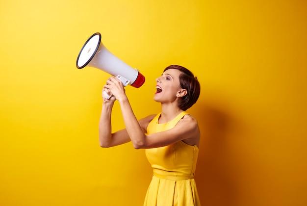 Modèle féminin à l'aide de mégaphone en séance photo