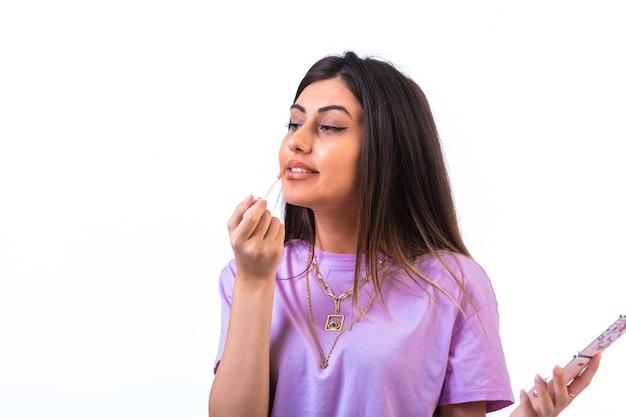 Modèle féminin appliquant le brillant à lèvres quotidien d'une manière positive