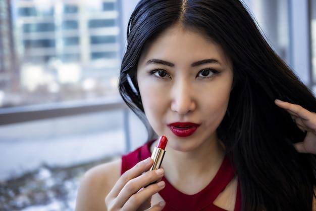 Modèle féminin asiatique porte une robe rouge sexy à la mode