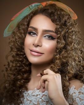 Modèle féminin aux cheveux bouclés et maquillage lumineux
