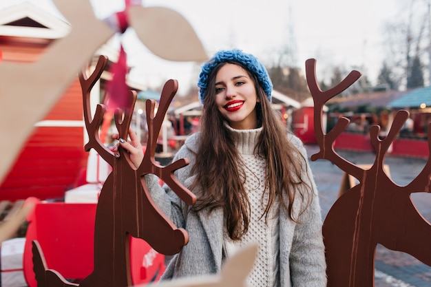 Modèle féminin aux cheveux noirs extatique appréciant noël dans un parc d'attractions à thème. portrait en plein air de fille heureuse en bonnet bleu tricoté posant près de décoration de vacances en hiver.