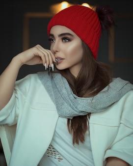 Modèle féminin en béret rouge et écharpe grise