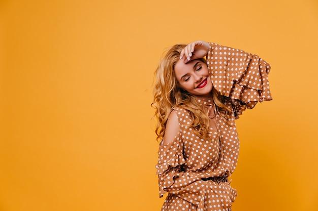 Modèle féminin blonde posant sur un mur jaune avec un sourire détendu. adorable jeune femme aux lèvres rouges glaçant