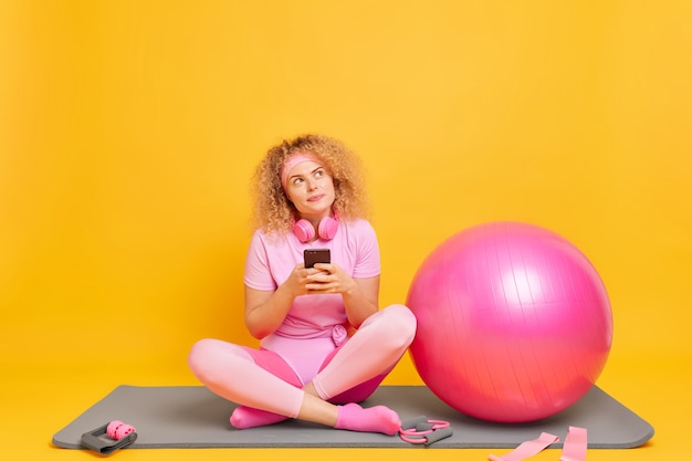 Un modèle féminin bouclé assez rêveur en bonne forme physique pose les jambes croisées sur un tapis de fitness prend une pause tout en faisant de l'exercice tient le téléphone portable reçoit un message texte