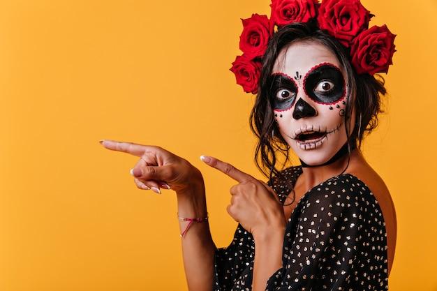 Modèle féminin bronzé en tenue d'halloween posant avec la bouche ouverte. superbe fille en tenue traditionnelle mexicaine célébrant le jour des morts.