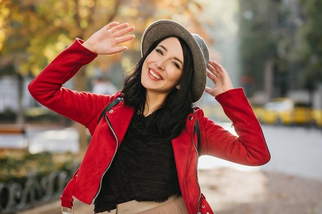Modèle féminin brune aux cheveux courts de bonne humeur marchant dans la rue en journée ensoleillée d'automne
