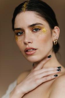 Modèle féminin brune calme posant dans des accessoires dorés. fille aux cheveux noirs à la mode avec du maquillage de fête.