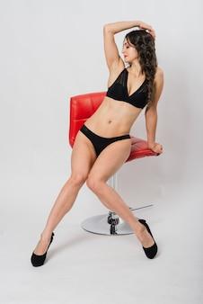 Modèle féminin brune mignonne posant, portant des sous-vêtements noirs et rouges dans un studio blanc