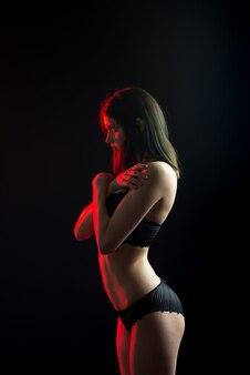 Modèle féminin brune mignonne posant, portant des sous-vêtements noirs en studio sombre