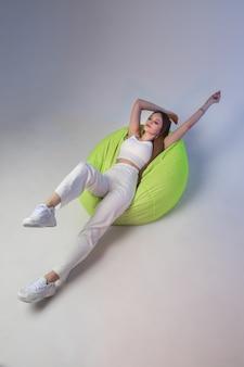 Modèle féminin caucasien à la mode en t-shirt blanc, pantalons de survêtement et baskets