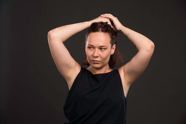 Modèle féminin en chemise noire collecte des poils.