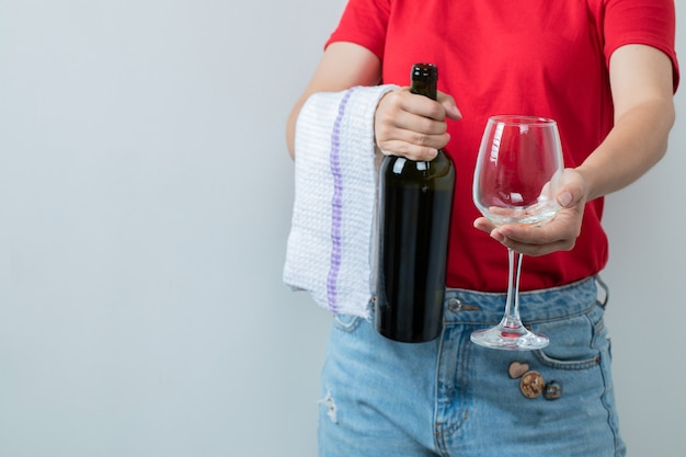 Modèle féminin en chemise rouge tenant une bouteille de vin avec verre.