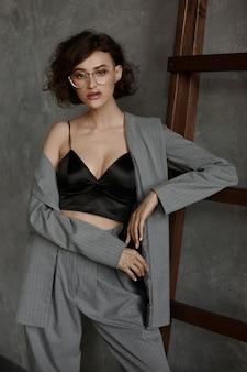 Modèle féminin avec un corps parfait et des lèvres charnues sexy portant un haut cami noir et un pantalon gris posant contre un mur gris