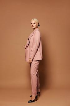 Modèle féminin élégant aux cheveux blonds en costume rose tendance et chaussures posant sur un fond beige tourné en studio d'une jeune femme en vêtements de style officiel