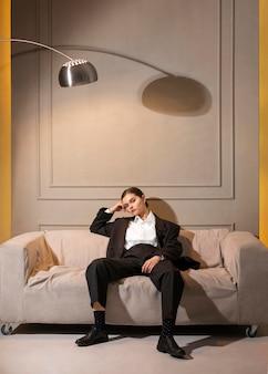 Modèle féminin élégant posant dans un canapé en costume de veste. nouveau concept de féminité