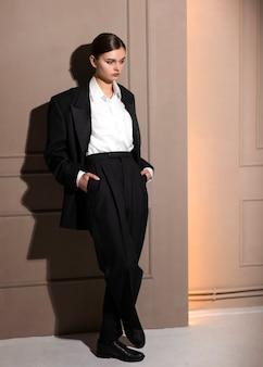 Modèle féminin élégant qui pose en studio en costume de veste. nouveau concept de féminité