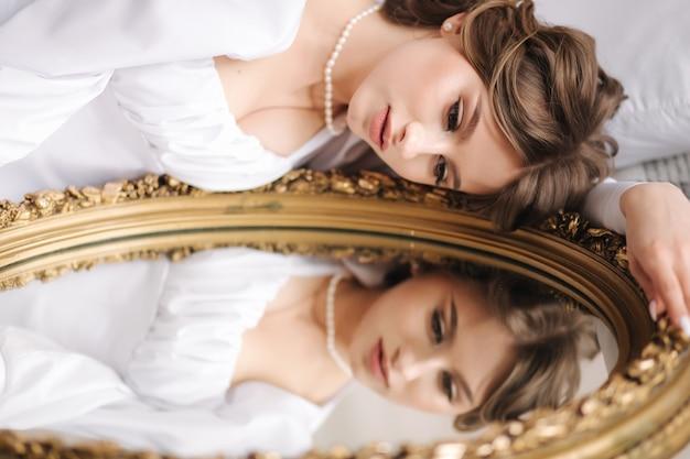 Modèle féminin élégant se trouve près du miroir avec son reflet mariée magnifique et sexy dans un court