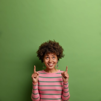 Un modèle féminin ethnique positif attire votre attention vers le haut, pointe les deux index sur un espace vide, suggère de cliquer ou de s'abonner, montre la place pour la promotion