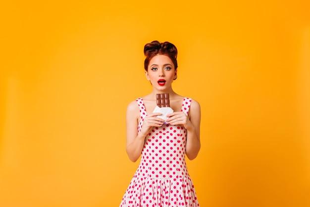 Modèle féminin étonné en robe à pois regardant la caméra. photo de studio de femme pin-up aux cheveux roux tenant du chocolat.