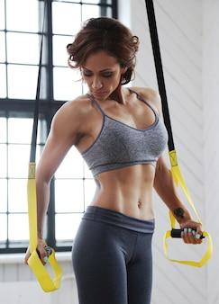 Modèle féminin faisant des activités sportives dans la salle de gym