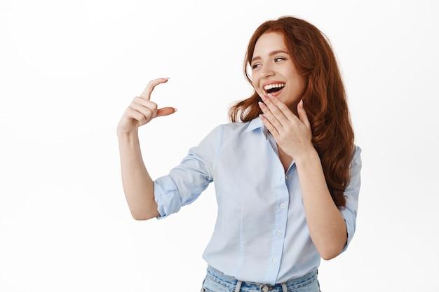 Modèle féminin heureux regardant une petite chose minuscule, montrant un petit geste de la main et riant, souriant heureux, debout en chemisier sur blanc