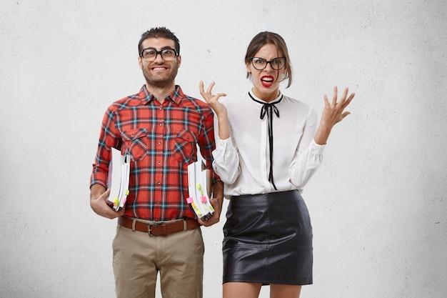 Un modèle féminin irrité fait des gestes avec les mains, ennuyé par l'homme wonk, qui essaie de lui apprendre