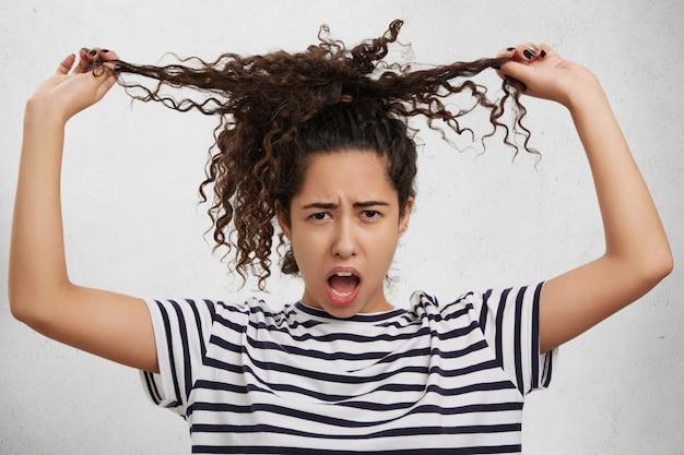 Un modèle féminin irrité garde la main sur des mèches bouclées, veut avoir les cheveux lisses, semble mécontent