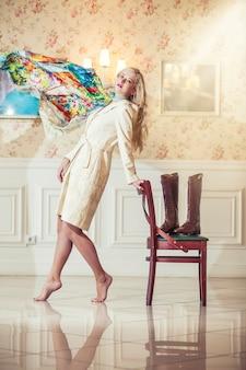 Modèle féminin en manteau lumineux avec un foulard volant et des lèvres rose vif dans un intérieur vintage