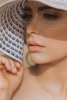 Modèle féminin en maquillage d'été avec des tons clairs