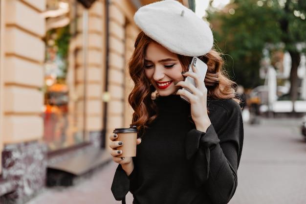 Modèle féminin mignon avec des cheveux ondulés au gingembre parlant au téléphone. dame française de bonne humeur posant avec un smartphone dans la rue.