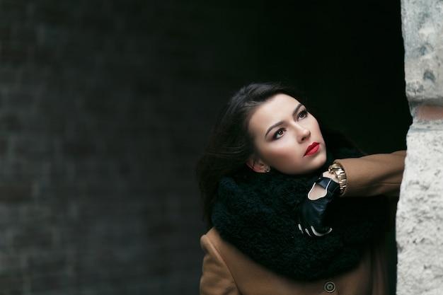 Modèle féminin de mode charmant dans un manteau.