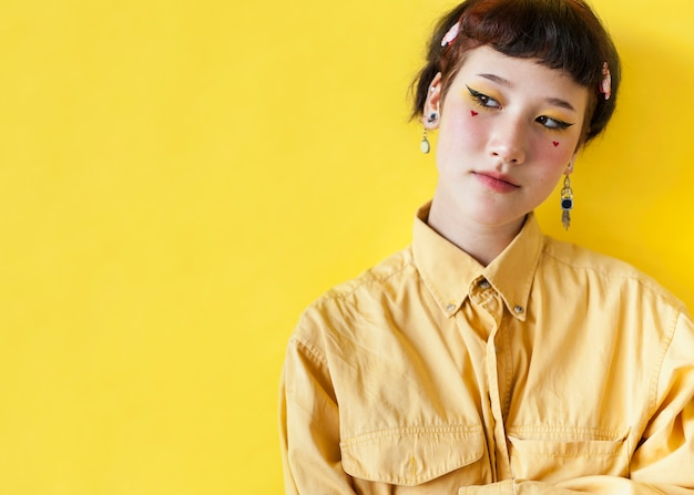 Modèle féminin à la mode qui pose en studio