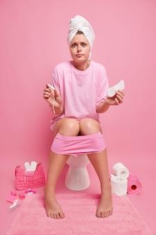 Un modèle féminin perplexe tient un tampon de coton menstruel et une serviette hygiénique porte une serviette enveloppée un t-shirt décontracté et une culotte noyée sur les jambes pose sur la cuvette des toilettes dans les toilettes sur le mur rose