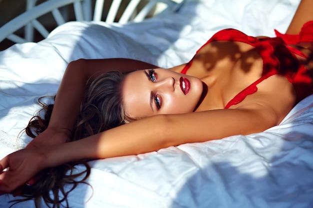 Modèle féminin portant de la lingerie rouge sur le lit le matin