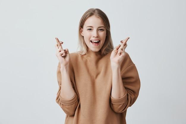 Modèle féminin positif attrayant avec des cheveux blonds croise les doigts comme des espoirs