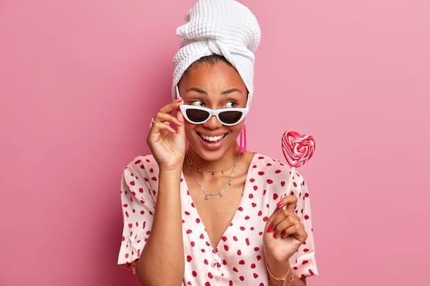 Modèle féminin positif porte des lunettes de soleil, vêtus de vêtements décontractés, tient une sucette en forme de coeur appétissante, regarde de côté avec une expression heureuse,
