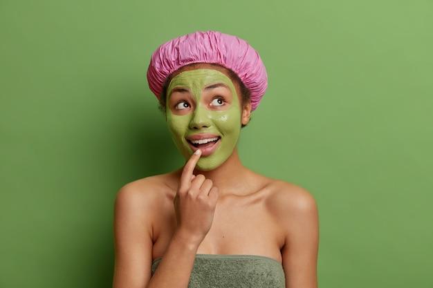Un modèle féminin réfléchi regarde joyeusement au-dessus garde le doigt sur les lèvres applique un masque facial de beauté isolé sur un mur vert a une expression pensive joyeuse