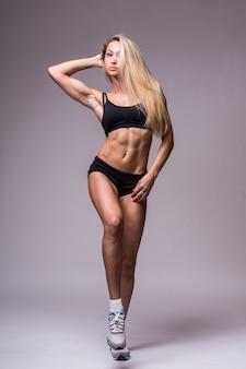 Modèle féminin de remise en forme en vêtements de sport sur fond gris