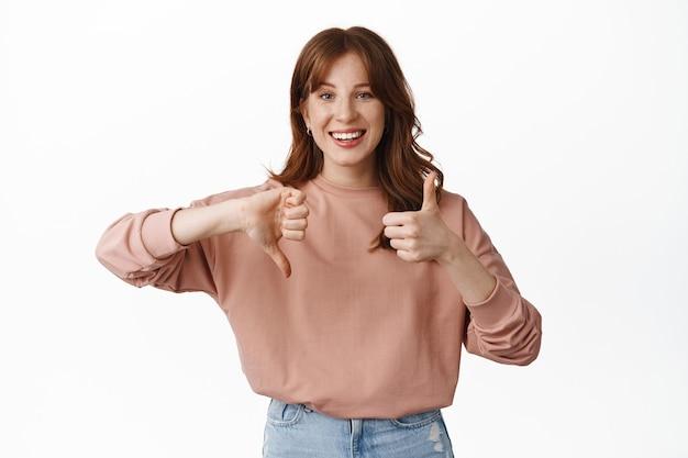 Modèle féminin rousse souriante, montrant le pouce vers le haut, taux moyen moyen, laisser des commentaires, debout sur blanc