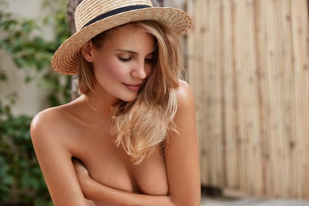 Un modèle féminin sérieux et réfléchi cache la poitrine avec les mains, a une peau saine et pure, regarde pensivement vers le bas, porte un chapeau d'été en paille, pose en plein air. nu jeune femme mince forme du corps parfait