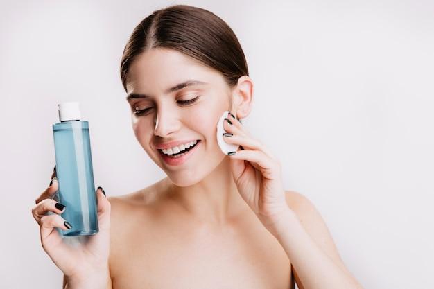 Modèle féminin avec un sourire blanc comme neige et sans maquillage pose sur un mur blanc, démontrant les propriétés bénéfiques de l'eau micellaire.