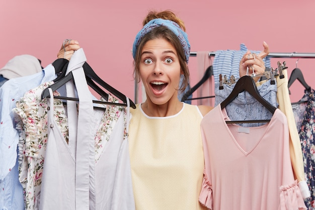 Modèle féminin surpris tenant de nombreux cintres avec des vêtements à la main, allant le mettre dans la cabine d'essayage, ne sachant pas quoi essayer en premier. choqué belle femme faisant du shopping dans un grand magasin